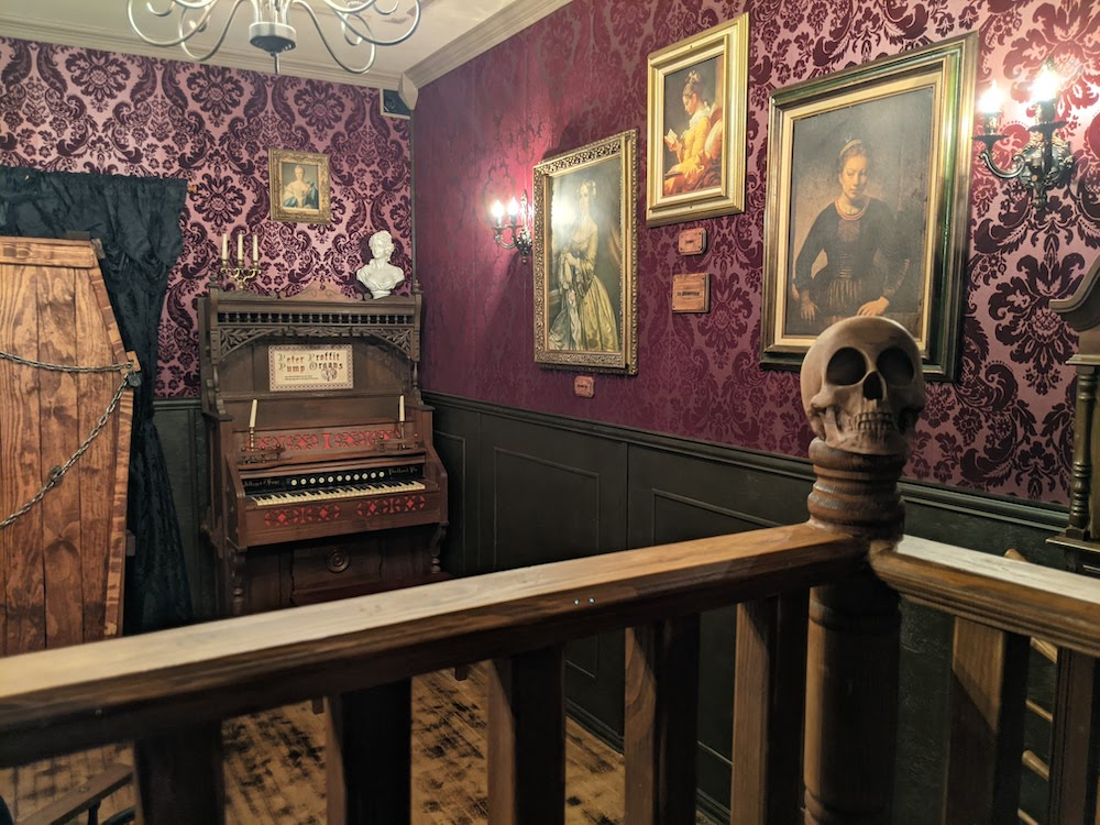 A skull on a railing in an ornate room with portraits hung on purple walls.