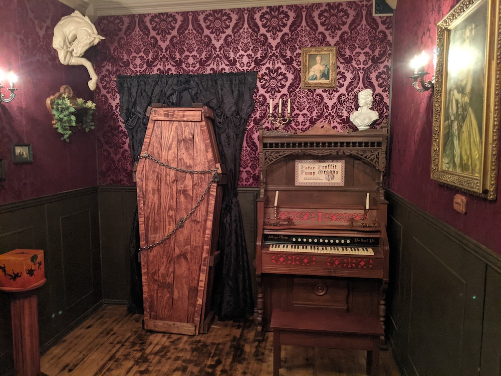 A coffin beside an organ in a very dramatic and ornate purple room.