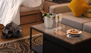 Image of a hotel room the morning after a fun night. Champagne, and room service dishes sit on a table beside an unmade bed with clothes on the floor.