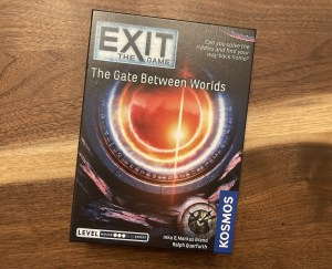 Exit The Game: The Gate Between Worlds box art has an orange portal set in a circular stone with symbols along the inner edge.