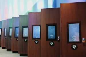 A line of check in stations, each with its own touch screen.