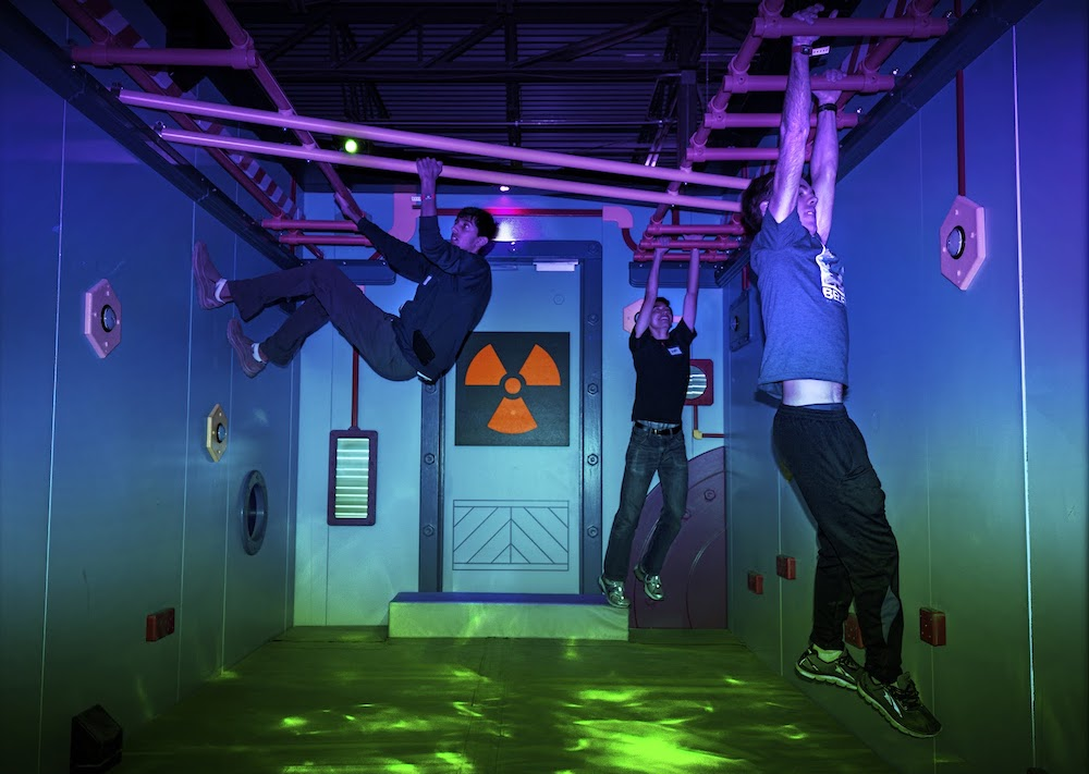 3 players hanging from monkey bars in a radiation themed game.