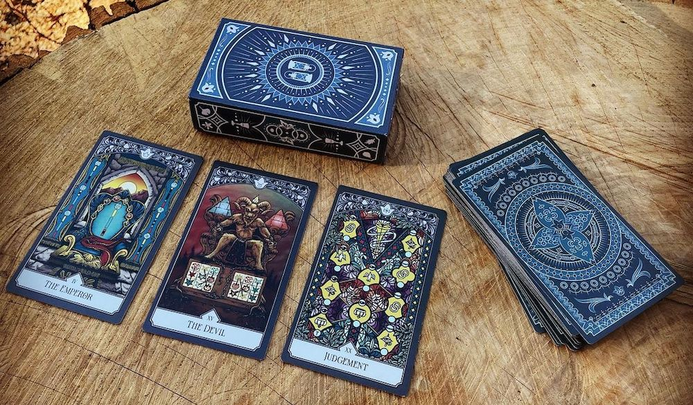 The deck, box, and 3 Major Arcana cards laying atop a tree stump.