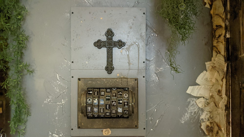 A large cross on a plaster wall, below it is a set of dials with different symbols.