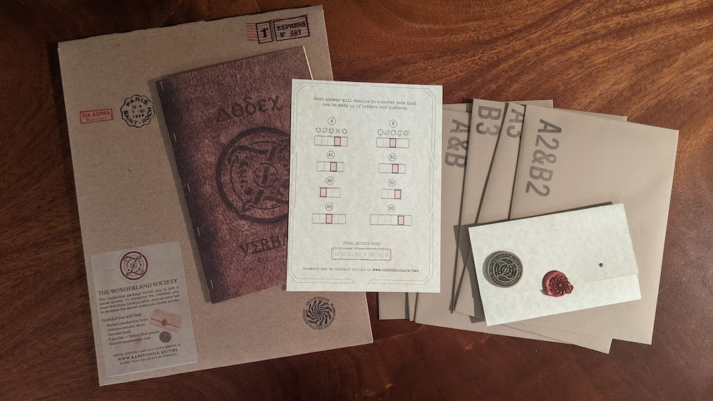 An assortment of envelopes with alphanumeric codes, an old looking journal, and an envelope with wax seal.