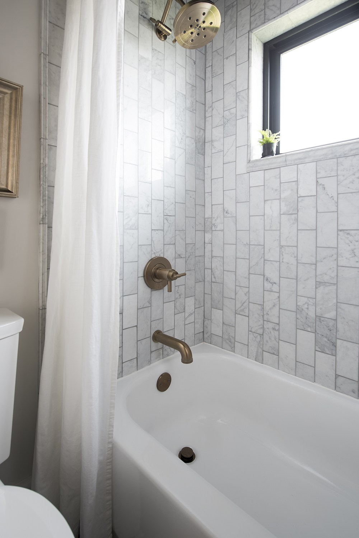 white bathtub brass plumbing fixtures