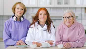 happy elderly women sitting at table with coffee