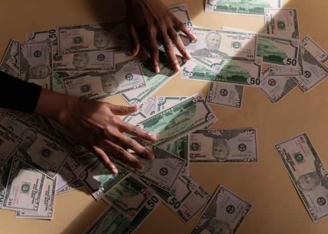 person holding fan of us dollar bill