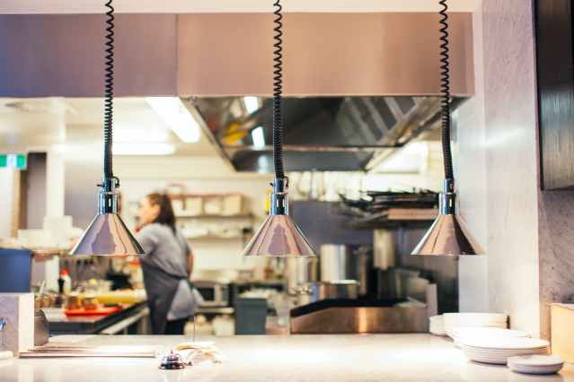 restaurant kitchen with faceless woman behind serving counter