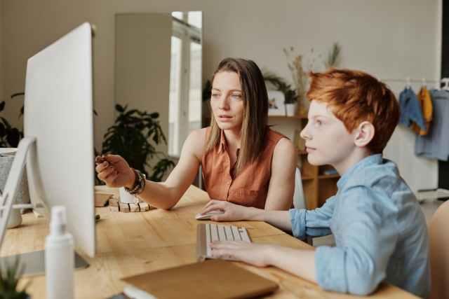 photo of woman tutoring young boy