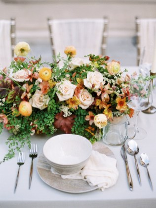 a bright and colorful centerpiece is on a neutral colored table. ranunculus and maiden hair fern are the flowers.