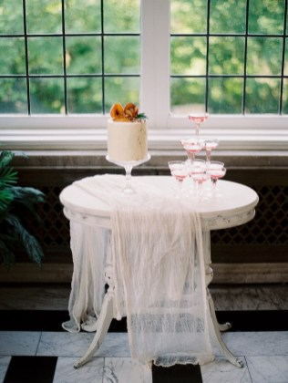 a cake and champagne tower sit in front of an iron framed window