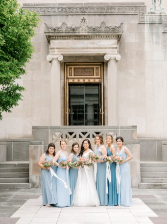 a bride and her bridesmaids stand in front of a stone building with their dusty blue bridesmaid dresses on and their floral bouquets full of spring flowers