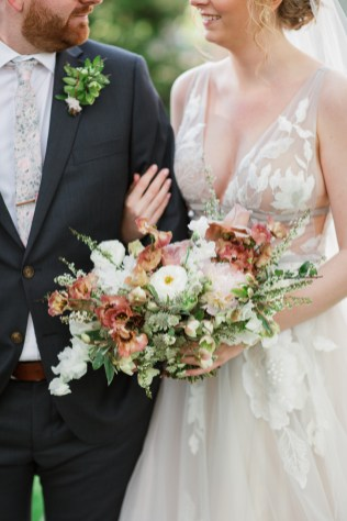 bride wearing a light grey wedding gown holds her spring bridal bouquet filled with dusty pink and blush blooms