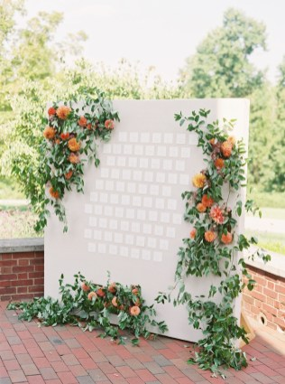 large escort card display surrounded by flowers and greenery to help guest find their seat at the reception at french park.