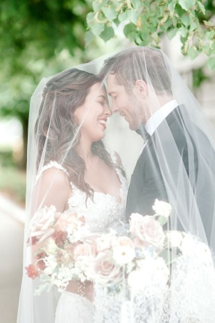 bride and groom smile underneath the veil under a tree at hotel covington in kentucky