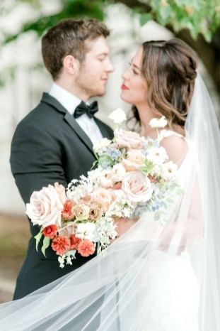 bride hold flower bouquet filled with in seasoned flowers like quicksand roses red butterfly ranunculus pink roses and blue delphinium and the lace veil swoops across the photo
