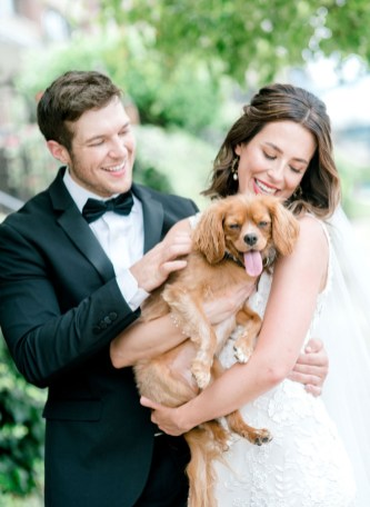 bride and groom hold their dog on their wedding day
