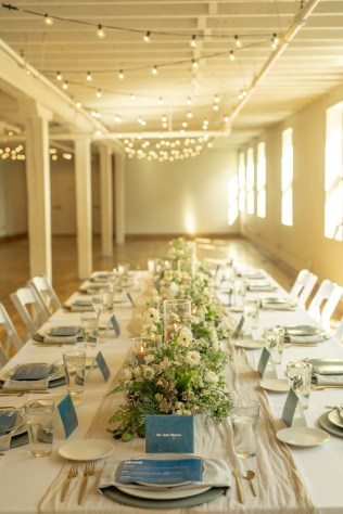 textural white and green floral centerpieces line the white linen table with blue place cards and menus with concrete chargers grey pillar candles in glass hurricanes and gold flatware at the factory events with bistro links and white columns with cincinnati wedding florist roots floral design