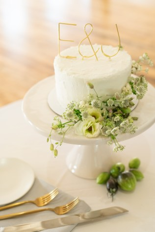 one layer cake with gold initials and flowers around the base of the cake on white cake stand