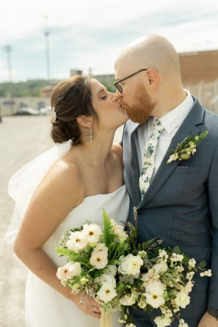 groom with navy suit and floral tie with textural boutonniere kisses the bride with her bouquet by cincinnati wedding florist roots floral design