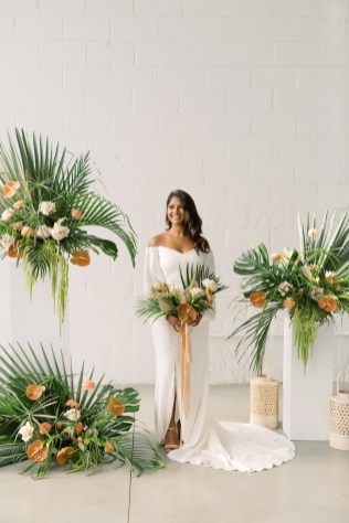african american bride stands in the middle of a stunning tropical ceremony installations with stands and lanterns against a white stone wall at mojave east flowers by cincinnati wedding florist roots floral design