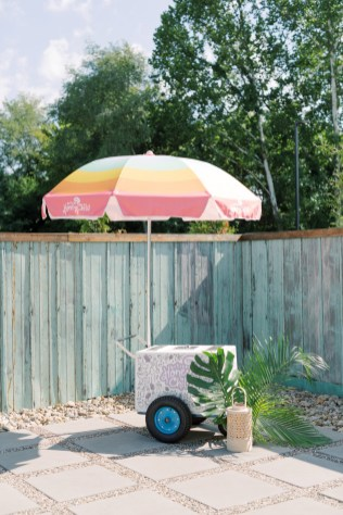 popsicle stand outside with large tropical leaves in the corner of the cart with wicker lantern