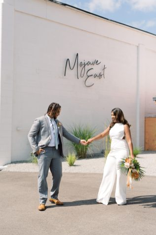 bride wearing a white jumpsuit joins hands with groom wearing a grey suit in from of the iron sign of mojave east in cincinnati