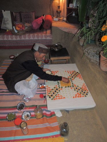 The priest makes a mandala out of grain for the pooja.