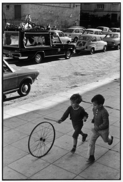 Photo by H. Cartier-Bresson of two children rolling a wheel.