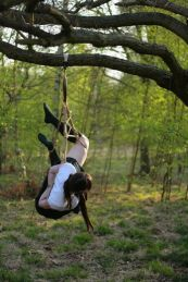 Shibari schoolgirl suspended in the park