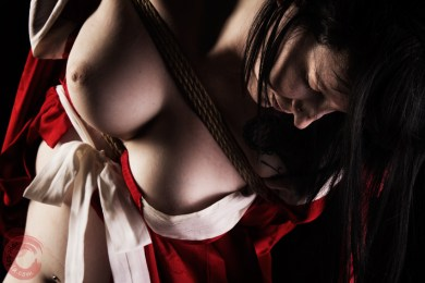Closeup shibari in red juban, tattooed model in takatekote. WykD method TK. Bondage images by WykD Dave & Clover.