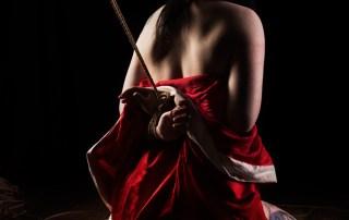 Shibari bondage emotion. Tattooed model tied in red juban. Bondage images by WykD Dave & Clover.