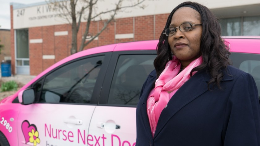 Nathalea stands in front of a Nurse Next Door company vehicle