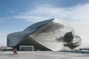 Louvers in the skin expose the glass envelope underneath, while allowing daylight to penetrate public spaces and airflow to naturally ventilate the building.