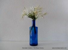 Botellas de cristal reutilizadas como floreros. Rosa Montesa