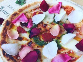 食べられる薔薇(白・ピンク・赤)をピザの上にまぶした食用バラの調理例