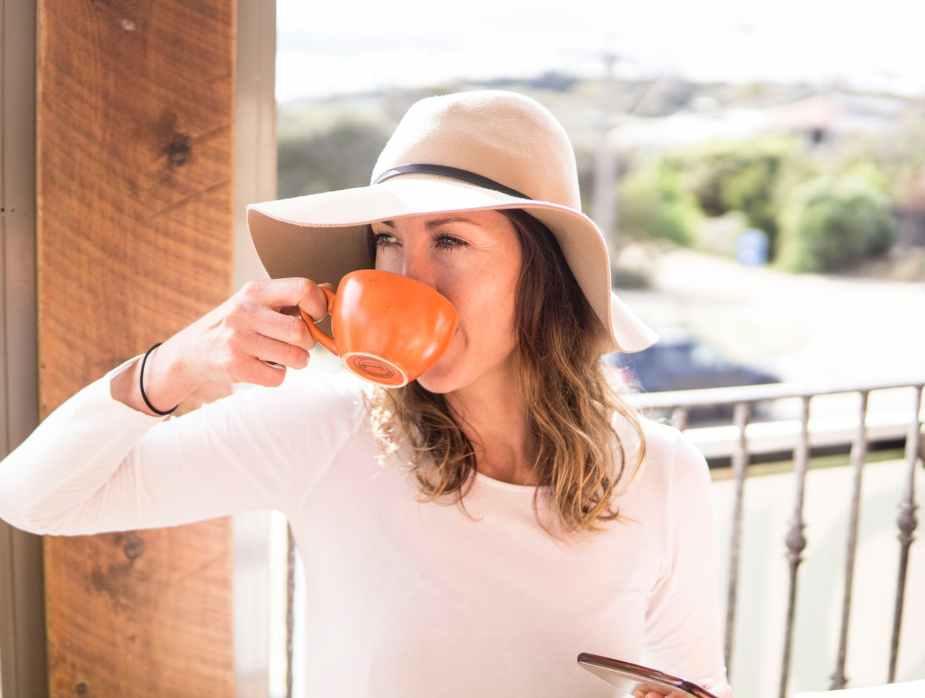 woman wearing hat holding mug