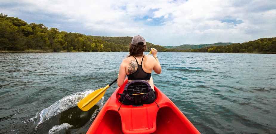 woman in black bikini top and brown hat sitting on red kayak