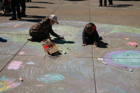 children in Calgary draw an earth on the sidewalk