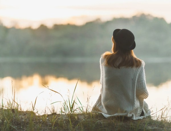 A girl sitting on the river bank in silence for self care. Self Care is Essential for the Soul