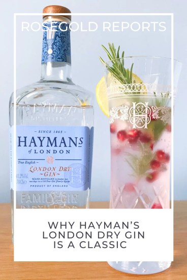A bottle of Hayman's London Dry gin, about 5/6th full with a branded glass next to it of gin and tonic with a sprig of rosemary, some pomegranite seeds and a slice of lemon. Superimposed is the text rosegold reports, and, Why Hayman's London Dry Gin is a classic