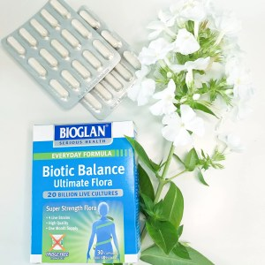 a box of bioglan biotic balance with two blister packs and a cut white flower