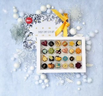 24 chocolates in a white box. The chocolates are different shapes (round, square, heart, leaf, tea cup, cherries) and decorated in different colours (white, orange, pink, blue, gold, green). They are surrounded by white Christmas baubles and decorations.