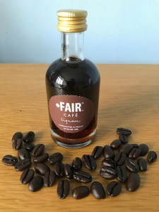 a small bottle of FAIR cafe liqueur with coffee beans in an arc in front