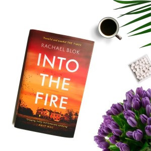 a copy of into the fire next to a cup off coffee and a bunch of purple tulips