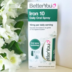A green and white carton containing better you iron oral spray, in the background green leaves and white orchids can be seen