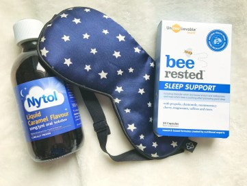 a bottle of nytol liquid, a box of bee rested and a blue silk eye mask is lying on a white blanket