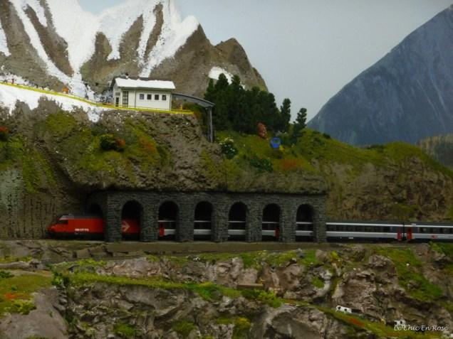 A miniature SBB Swiss rail train passes through an avalanche protection tunnel