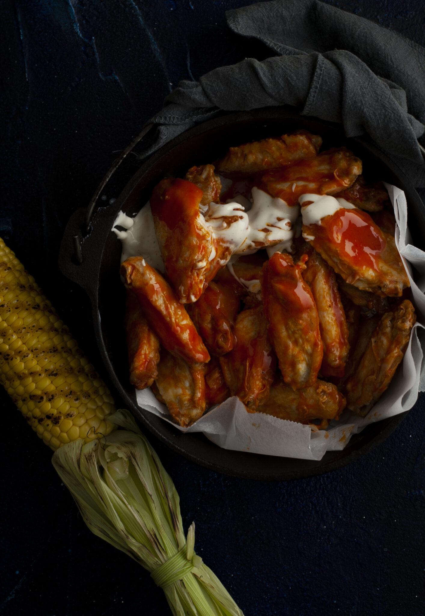 donkere foodfoto van gietijzeren pan met chcikenwings en maiskolf met grillstrepen